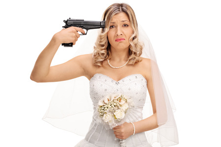 holding gun to head: Young desperate bride holding a gun against her head and looking at the camera isolated on white background