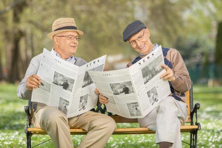 oude krant: Senior man toont iets in de krant naar een vriend gezeten op een houten bankje in een park