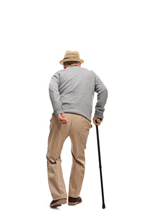 Rear view vertical shot of an aged man walking with a black cane isolated on white background