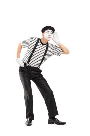 Vertikale Schuss von einem männlichen Pantomime versucht, etwas zu hören, isoliert auf weißem Hintergrund