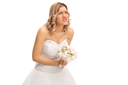 experiencing: Studio shot of a young bride experiencing pain in her abdomen isolated on white background