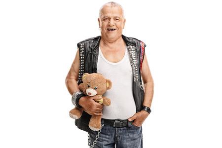 rocker: Studio shot of a mature punk rocker holding a teddy bear isolated on white background Stock Photo