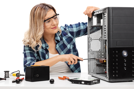 desktop computer: Young blond woman fixing a desktop computer seated at a table isolated on white background Stock Photo