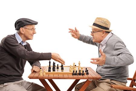 jugando ajedrez: Dos ancianos jugando una partida de ajedrez aisladas sobre fondo blanco Foto de archivo