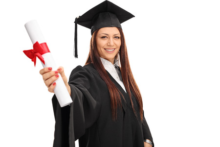 gown: Studio shot of a young woman in a graduation gown holding a diploma isolated on white background Stock Photo