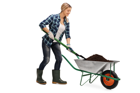 shoveling: Young blond woman shoveling dirt out of a wheelbarrow isolated on white background