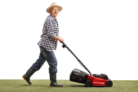 Profiel shot van een volwassen man het maaien van een gazon met een grasmaaier op een witte achtergrond