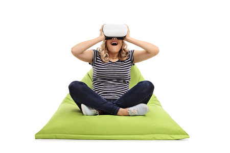 beanbag: Excited woman using VR goggles seated on a green beanbag isolated on white background Stock Photo