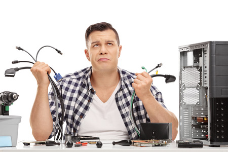 baffled: Baffled young guy holding a bunch of computer wires and looking up isolated on white background