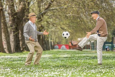 Twee blije senioren voetballen in een park op een mooie lentedag Stockfoto
