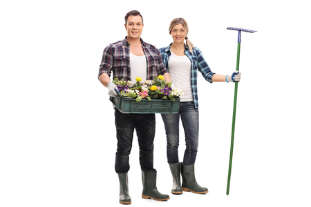 Young man and a woman posing together with gardening equipment and flowers isolated on white background