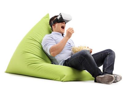젊은 남자 팝콘을 먹고 흰색 배경에 고립 된 콩 주머니에 앉아 가상 현실 고글에 뭔가보고