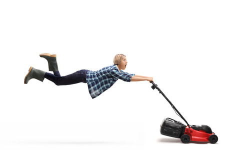 Young female gardener being pulled by a powerful lawnmower isolated on white background Stock Photo
