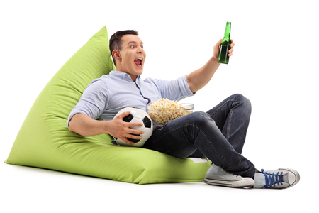 watching: Studio shot of a young soccer fan watching a game with beer and popcorn seated on a beanbag isolated on white background
