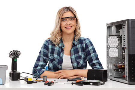 it technician: Female PC technician posing seated at a table with a bunch of tools on it isolated on white background Stock Photo