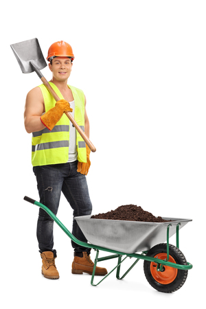shovel in dirt: Vertical shot of a young construction worker holding a shovel next to a wheelbarrow full of dirt isolated on white background
