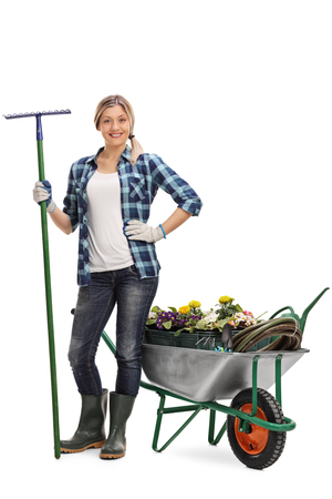 Full length portrait of a woman holding a rake and posing next to a wheelbarrow full of gardening equipment and flowers isolated on white background Stock Photo