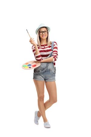 paleta de pintor: longitud completa tiro vertical de una bella mujer joven sosteniendo un pincel y una paleta de colores aislados sobre fondo blanco