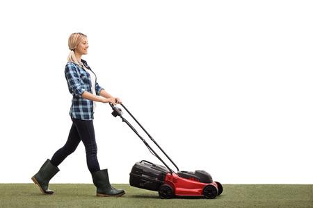 흰색 배경에 고립 lawnmower와 잔디를 깎고 쾌활 한 젊은 여자의 프로필 샷