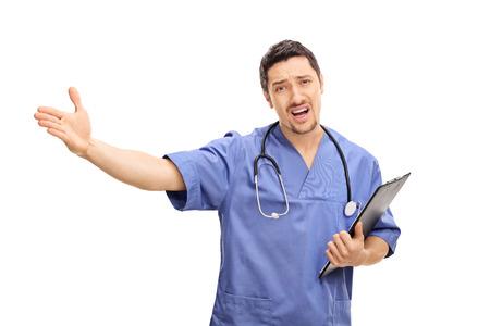 irrespeto: disgustado médico joven que sostiene un sujetapapeles y haciendo un gesto con la mano aisladas sobre fondo blanco