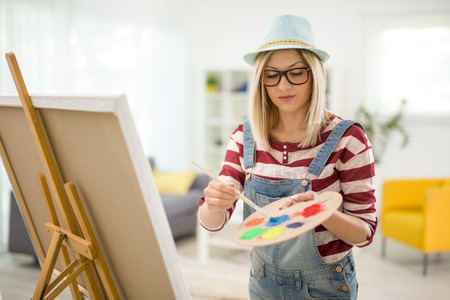 canvas painting: Young female artist mixing colors on a palette and painting on a canvas at home Stock Photo