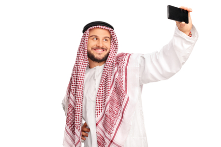 studio picture: Modern Arab taking a selfie with cell phone and smiling isolated on white background