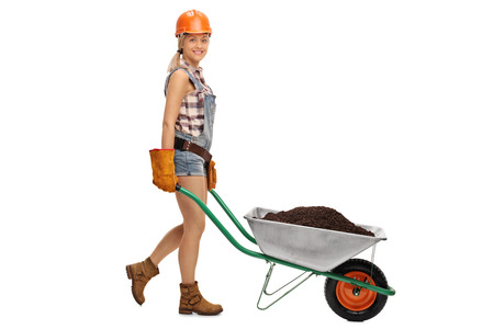 dirt background: Female construction worker pushing a wheelbarrow full of dirt and looking at the camera isolated on white background Stock Photo
