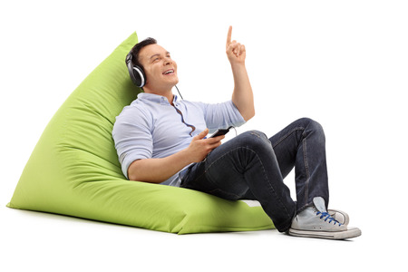 beanbag: Young guy listening to music on headphones seated on a green beanbag isolated on white background