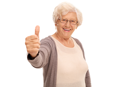 posing  agree: Elderly woman giving a thumb up and looking at the camera isolated on white background Stock Photo