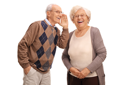 El estudio tiró de un viejo hombre que susurra algo a su mujer aislado en el fondo blanco Foto de archivo