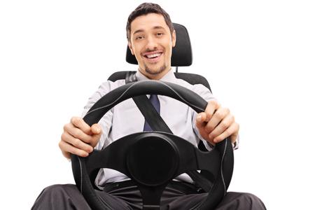 persona sentada: Individuo alegre que sostiene un volante sentado en un asiento de coche aislado en el fondo blanco