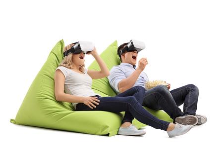 Opgewonden jonge paar het ervaren van virtual reality gezeten op zitzakken op een witte achtergrond