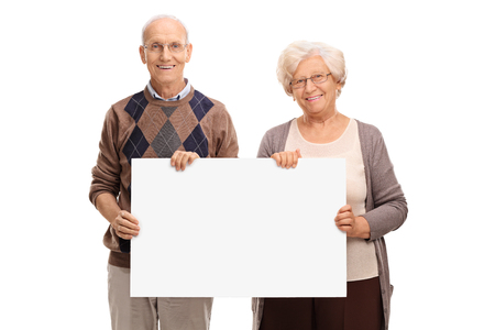 white poster: Senior couple posing together and holding a blank white signboard isolated on white background