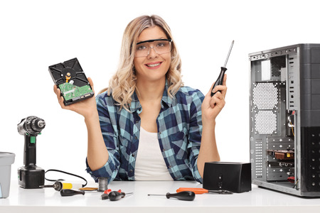 repaired: Cheerful female IT technician holding a computer part and a screwdriver isolated on white background