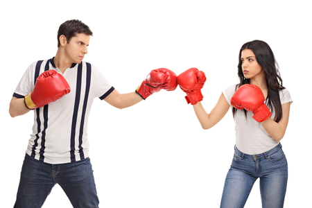 competing: Man and woman with boxing gloves standing opposite of each other isolated on white background Stock Photo