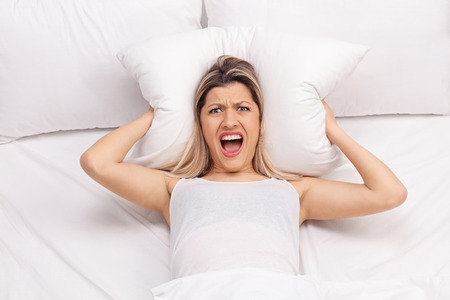 molesto: Mujer furiosa tapándose los oídos con una almohada y tratando de dormir