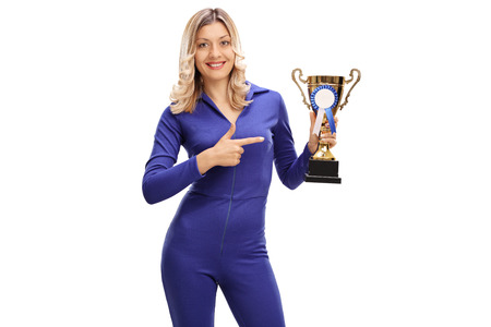 presenting: Young woman in a blue racing suit holding a trophy and pointing towards it isolated on white background Stock Photo