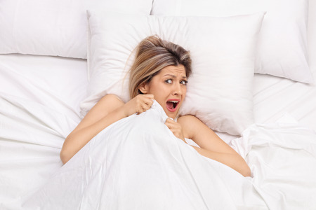 woman in bed: Scared young woman lying in bed covered with a blanket and screaming