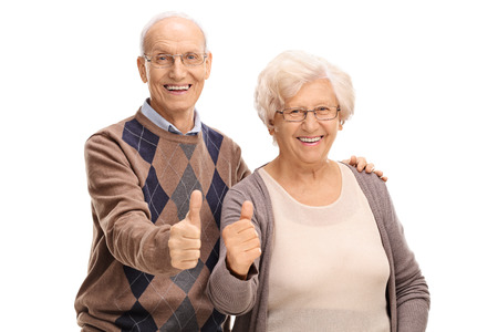 posing  agree: Senior man and woman giving thumbs up and looking at the camera isolated on white background