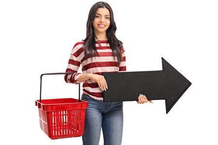 Junge Frau mit einem leeren Warenkorb und einen Pfeil hält rechts zeigt auf weißem Hintergrund