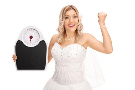 Alegre novia que sostiene una escala del peso y hacer gestos felicidad aislado en el fondo blanco Foto de archivo