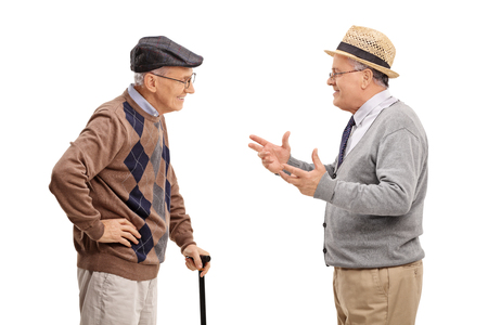 two men: Two senior gentlemen talking to each other and smiling isolated on white background Stock Photo
