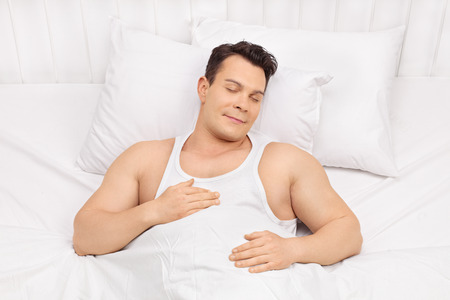 comfortable: Happy young man sleeping on a comfortable bed and dreaming Stock Photo