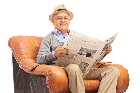 Content senior gentleman reading a newspaper seated on a comfortable armchair isolated on white background