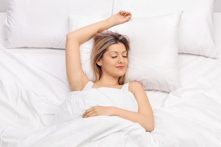comfortable: Joyful young woman sleeping on a comfortable bed and smiling Stock Photo