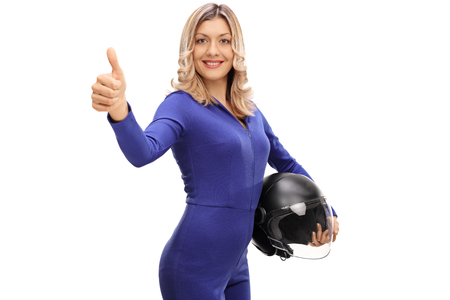 posing  agree: Attractive female car racer holding a helmet and giving a thumb up isolated on white background Stock Photo