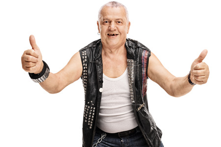 posing  agree: Mature man in an old punk leather jacket with pins giving thumbs up isolated on white background