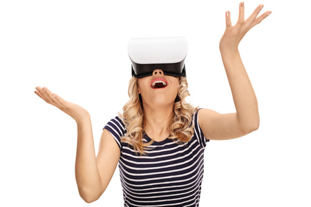 white people: Amazed young woman looking in a VR goggles and gesturing with her hands isolated on white background