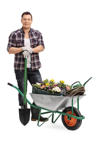carretilla: Retrato de cuerpo entero de un hombre joven que presenta con el equipo de jardinería aislados sobre fondo blanco