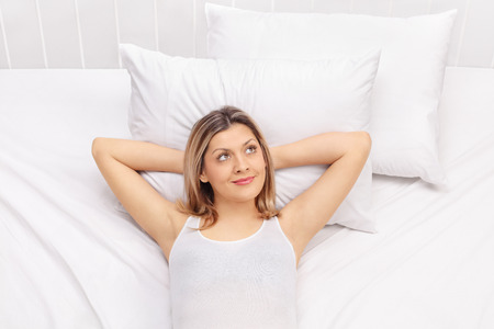 carefree: Carefree young woman laying on a comfortable bed and daydreaming Stock Photo